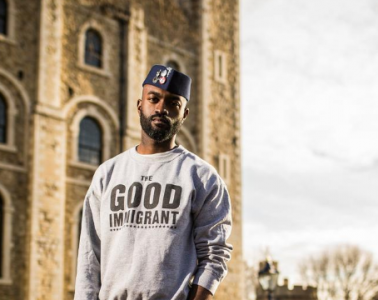Inua Ellams stands in outside an old building, his jumper reads 'The Good immigrant'
