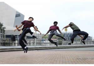 Three male dancer outside in mid leap wearing jeans and t-shirt