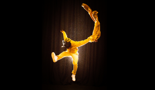 A man in mid leap in a yellow jump suit on a black background