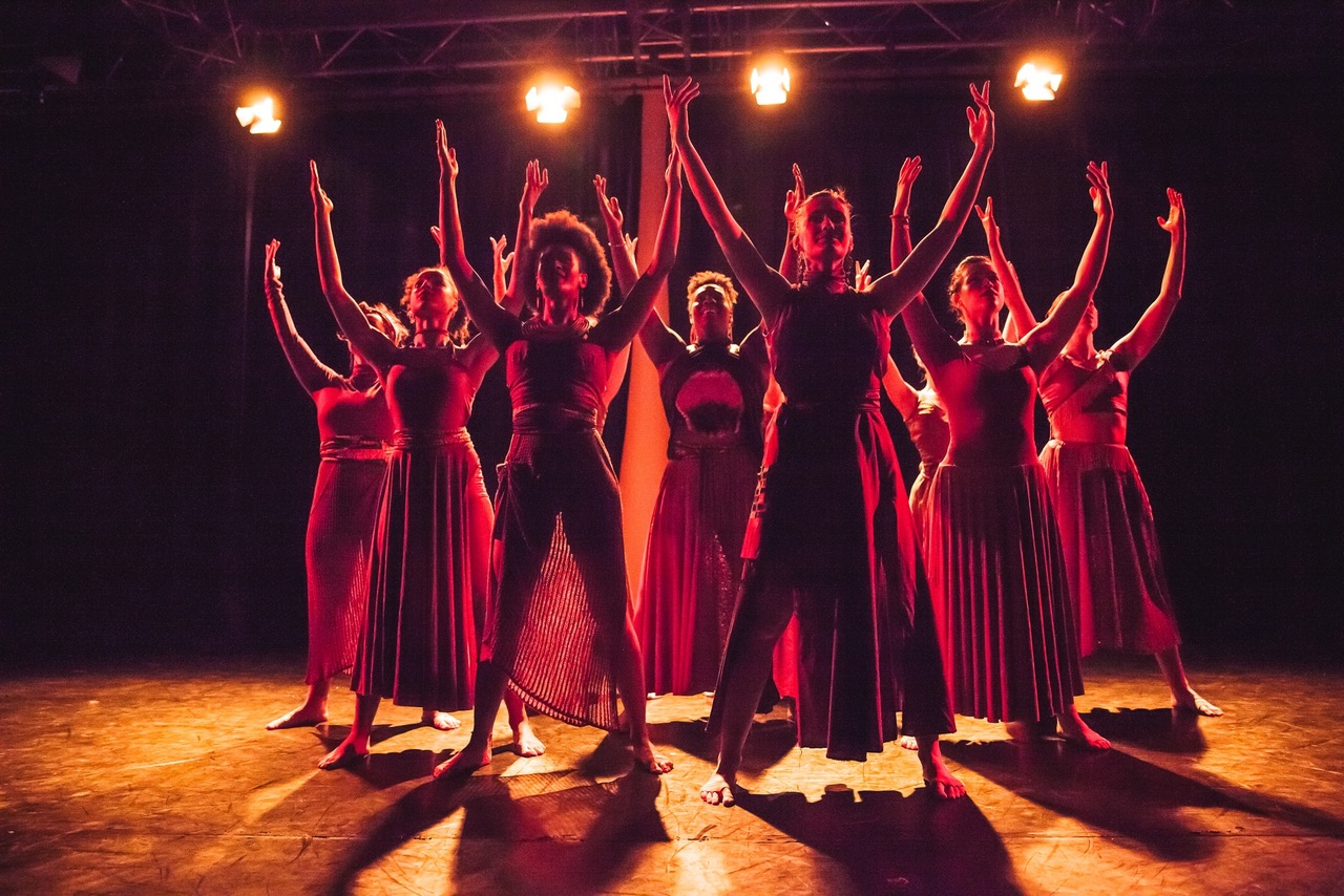 A group of dancers stood on stage lit in a red light with their hands up.