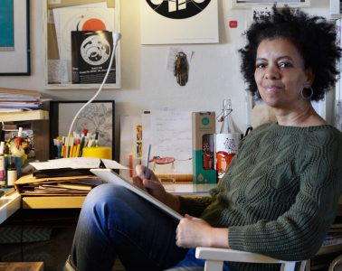 A woman sat in illustration studio at a desk with a notepad on her lap