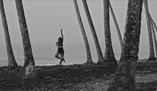 A black and white image of a woman on a beach in pose stood on one leg with one arm pointing up.